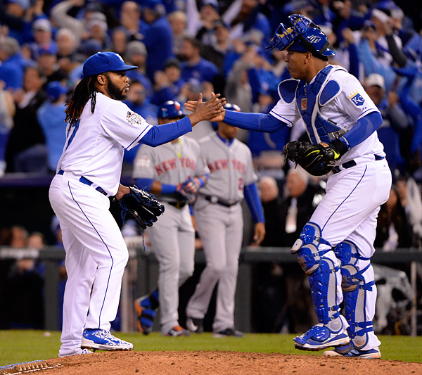 Johnny Cueto and Salvidor Perez celebrate as the Royals defeated the Mets 7-1 during Game Two of the 2015 World Series at Kaufmann Stadium in Kansas City, MO. (Photo by Ron Vesely/MLB Photos)