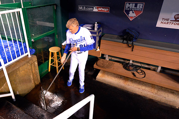 Royals first base coach Rusty Kuntz does a little house keeping prior to Game One of the 2015 World Series. (Photo by Ron Vesely/MLB Photos)