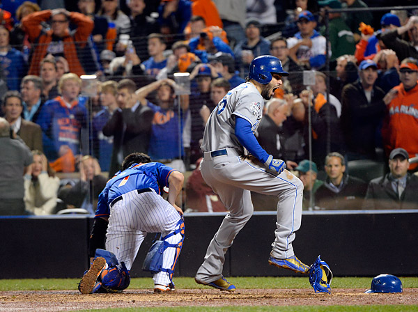The Kansas City Royals Eric Hosmer celebrates as Mets fans collectively hold the heads in disbelief after Hosmer scored the tying run in the bottom of the ninth inning after Lucas Duda of the New York Mets threw the ball wildly past Mets catcher Travis d'Arnaud during Game Five of the 2015 World Series. (Photo by Ron Vesely/MLB Photos)