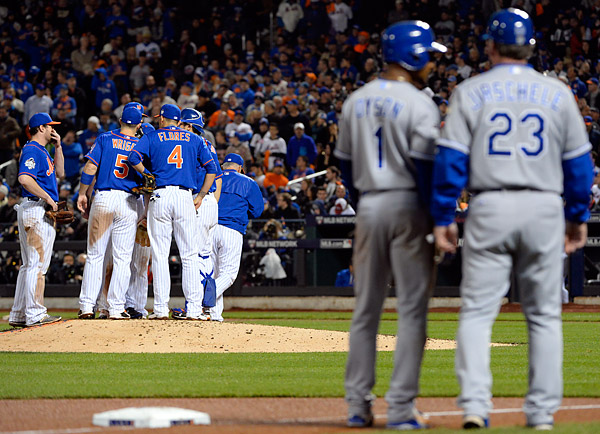 Kansas City Royals pinch runner Jarrod Dyson looks on from third as the Mets gather to on the mound during Game Five of the 2015 World Series. (Photo by Ron Vesely/MLB Photos)